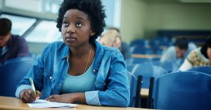 Female student listening attentively to the teacher in a room.