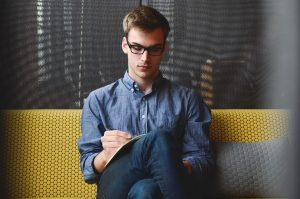 Young man writing while sitting on a couch.
