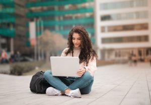 Female student sitting on the cement floor of a campus.