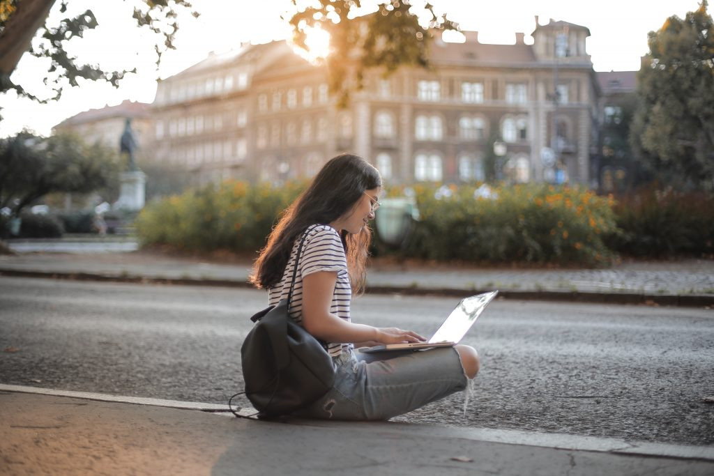 Female student doing her research in front of a building.