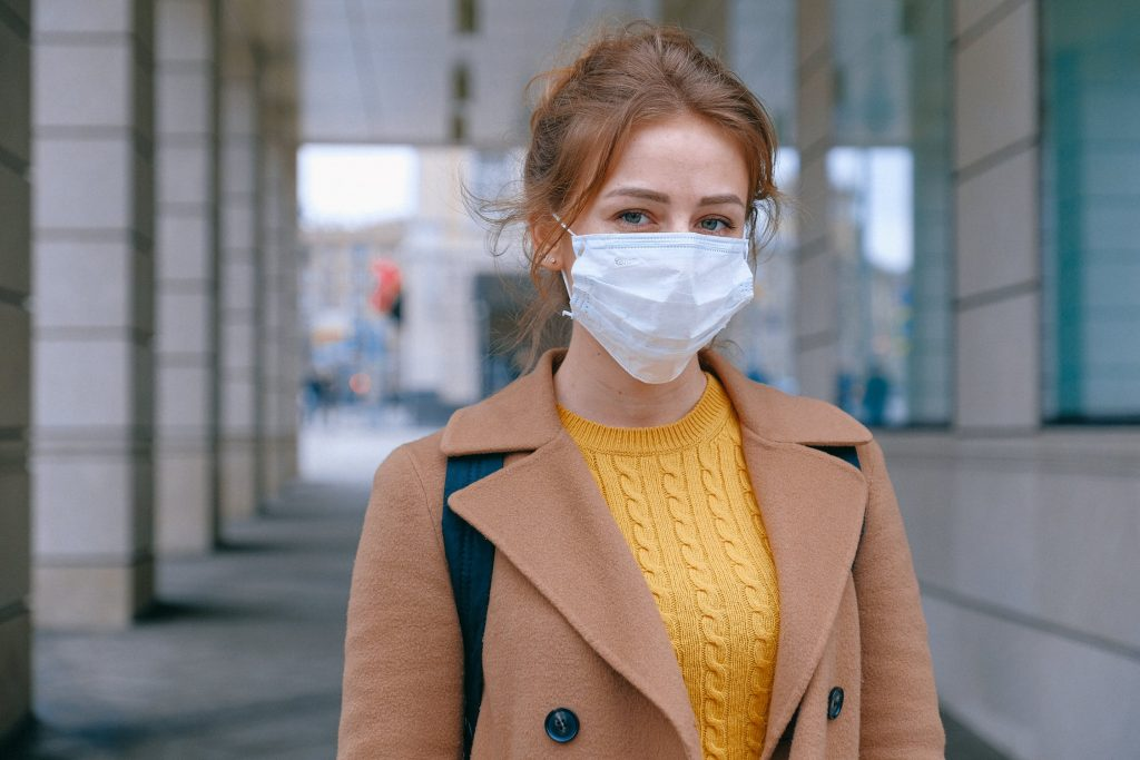Young woman wearing a mask outside a building to protect herself from COVID-19.