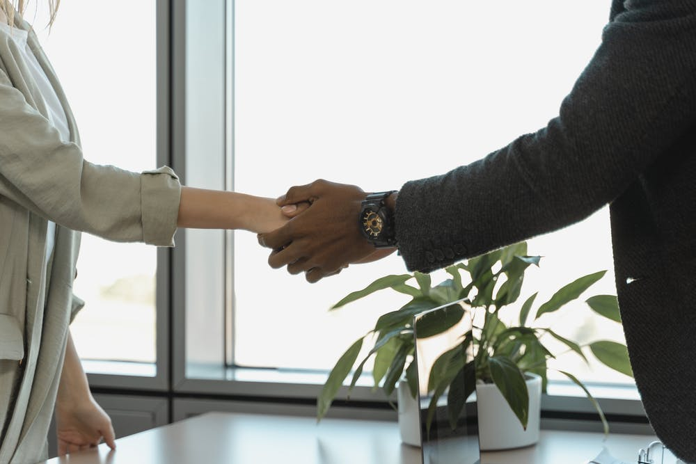 Unknown people shaking hands in an office.