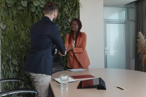 Young woman shaking the hand of a man for a job interview.