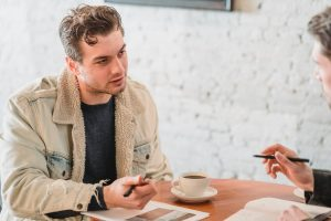 Student talking to someone on a coffee shop for a job.