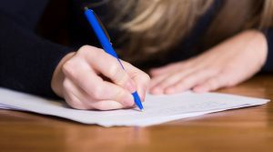 Woman writing on a paper using a pen.