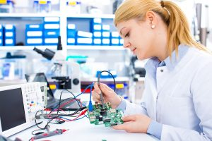 Female student repairing electronic device on the circuit board.