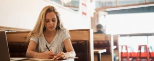 Female student writing in a diner.