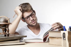 Male student studying with his books.