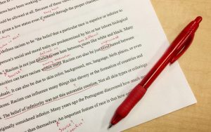 Proofreading a paper using a red pen.