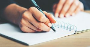 Writing in a notebook using a pen.