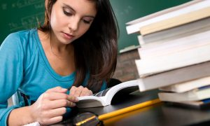 Female student studying in a table with books.