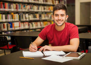 College student writing in a library.