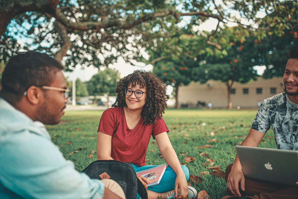 Three students talking in the school grounds.