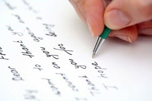 Writing in a paper using a pen.