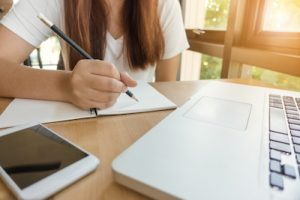 Female student writing on her study table with a laptop.