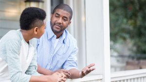 Student and parent talking near a window.