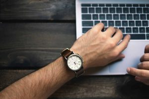A hand with a watch near a laptop.
